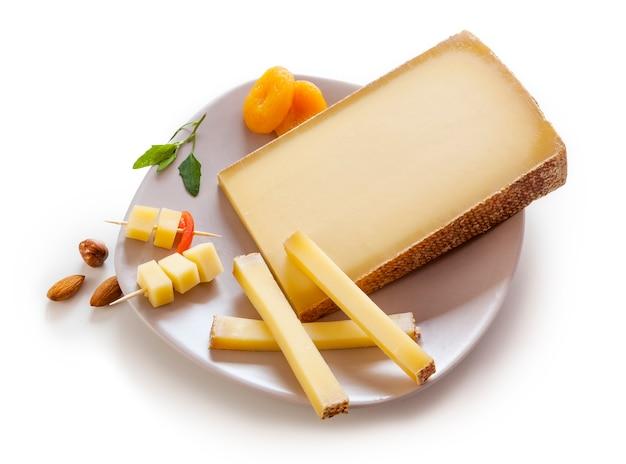 白い背景の上のプレートにスイスグリュイエールチーズ 無料写真