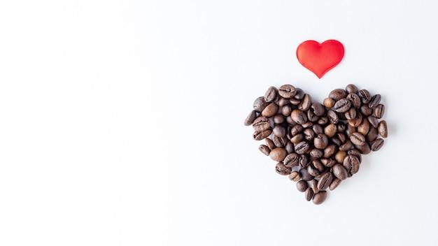 Символ любви к кофе. форма сердца из кофейных зерен и красного сердца на белом фоне Premium Фотографии