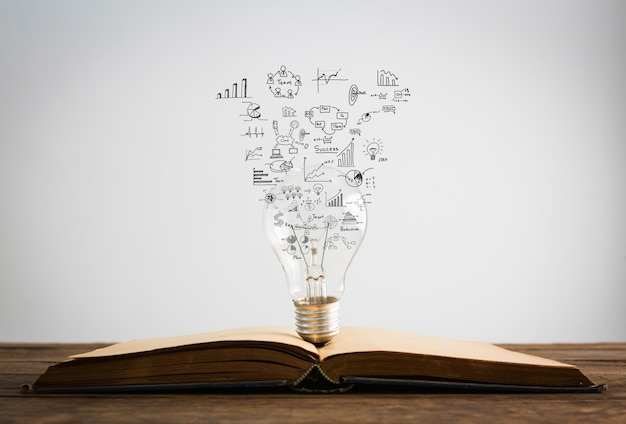 Symbols come out of a bulb on top of a book Free Photo