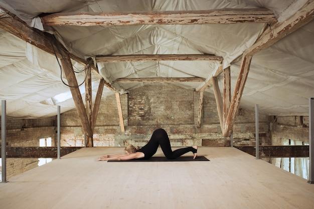 Simmetria. una giovane donna atletica esercita lo yoga su un edificio abbandonato. equilibrio della salute mentale e fisica. concetto di stile di vita sano, sport, attività, perdita di peso, concentrazione. Foto Gratuite