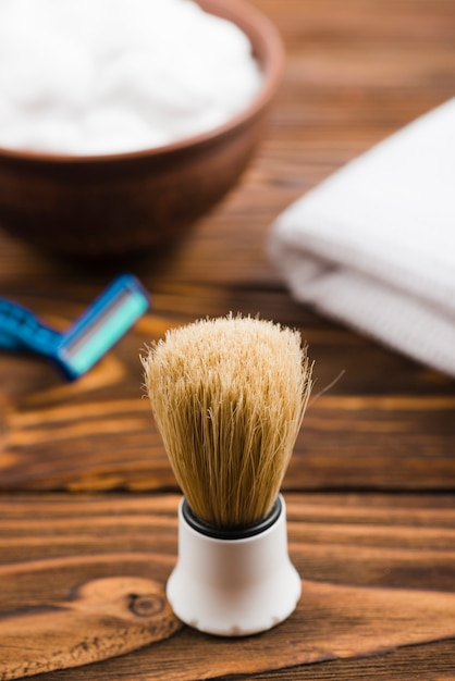 Synthetic shaving brush with foam; razor and folded napkin at background on table Free Photo