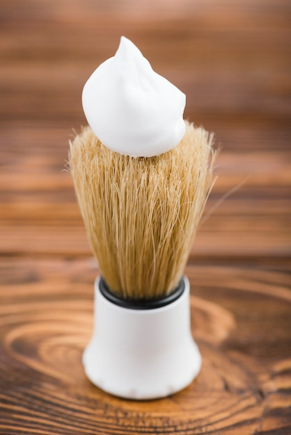 Synthetic shaving brush with on wooden table Free Photo