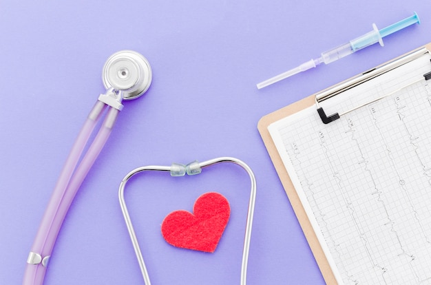 Syringe; medical report on clipboard; heart with stethoscope on purple background Free Photo