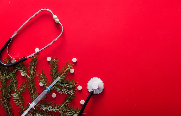 Шприц таблетки маска стетоскоп и ветви елки Premium Фотографии