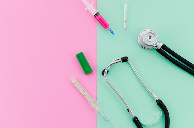 Syringe; stethoscope; thermometer on pink and mint green background Free Photo