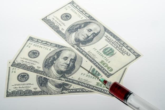 Шприц с кровью на белом фоне с деньгами Premium Фотографии