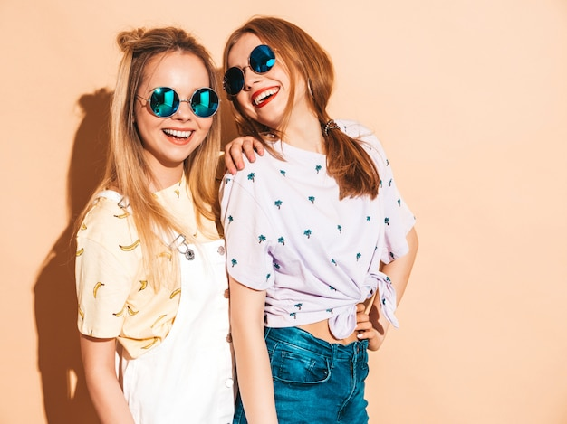 トレンディな夏のカラフルなtシャツの服の2人の若い美しい笑顔金髪流行に敏感な女の子。 無料写真