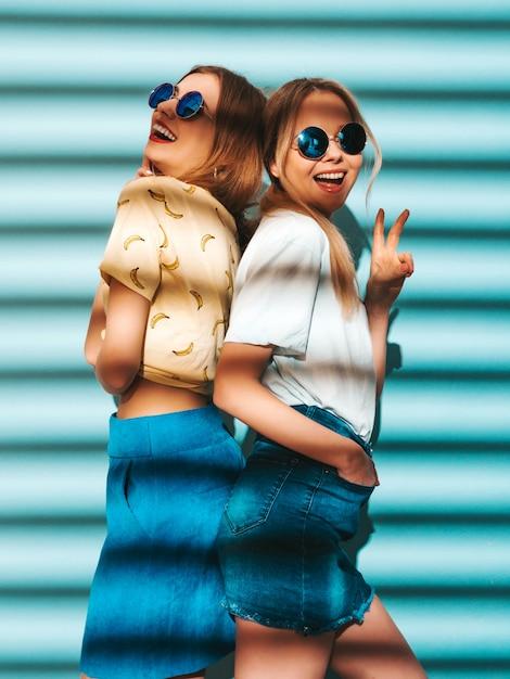 トレンディな夏のカラフルなtシャツの服の2人の若い美しい笑顔金髪流行に敏感な女の子。丸いサングラスで青い壁に近いポーズセクシーな屈託のない女性。ピースサインを示す肯定的なモデル 無料写真