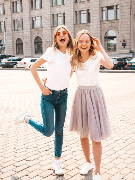 トレンディな夏の白いtシャツ服で流行に敏感な女の子を笑顔2つの若い美しいブロンドの肖像画。 無料写真