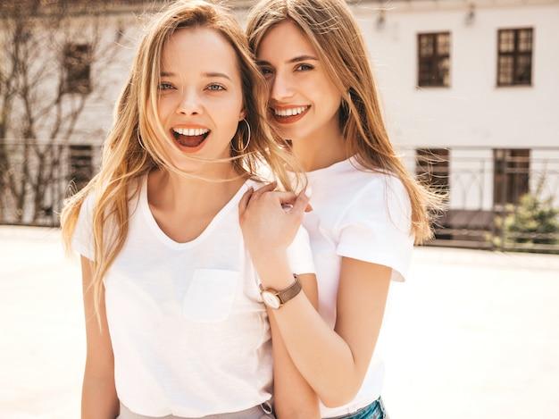 トレンディな夏の白いtシャツ服で流行に敏感な女の子を笑顔2つの若い美しいブロンドの肖像画。 。楽しいポジティブなモデル 無料写真