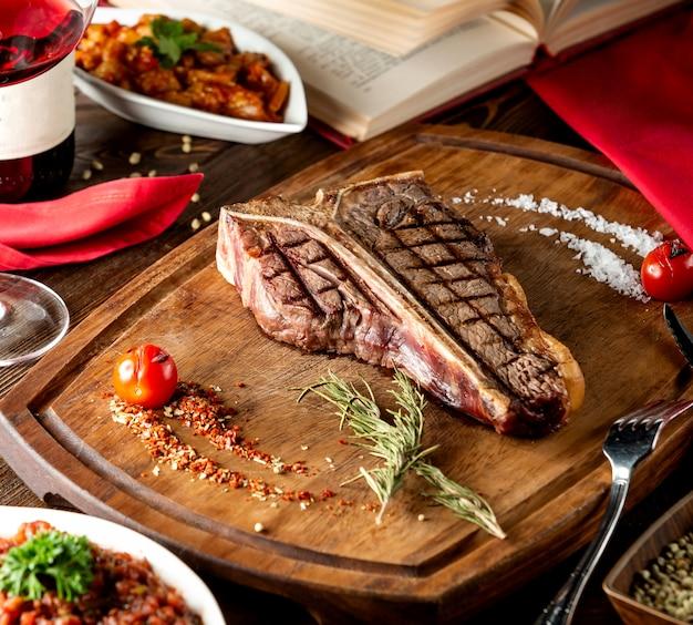 T-bone steak served in wooden board with slat rosemary Free Photo