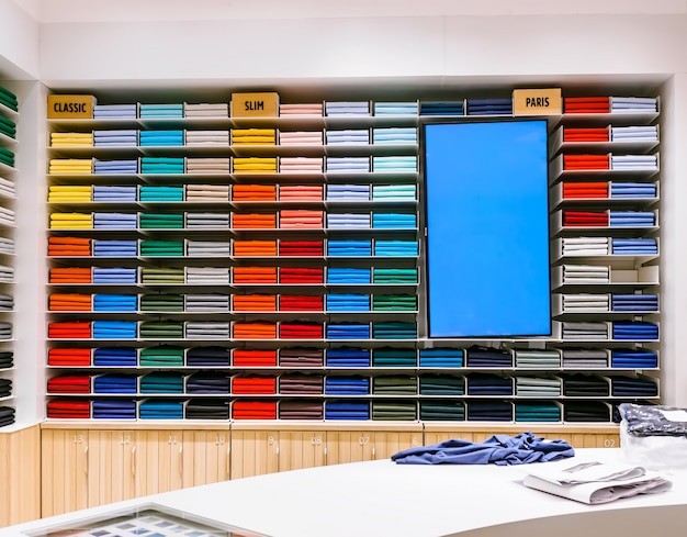 T-shirt of different color are neatly stacked in a row on the store shelves around promotional screen Premium Photo