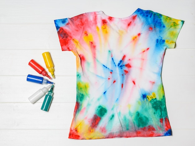 T-shirt painted in tie dye style with colors on a white wooden table. flat lay. Premium Photo
