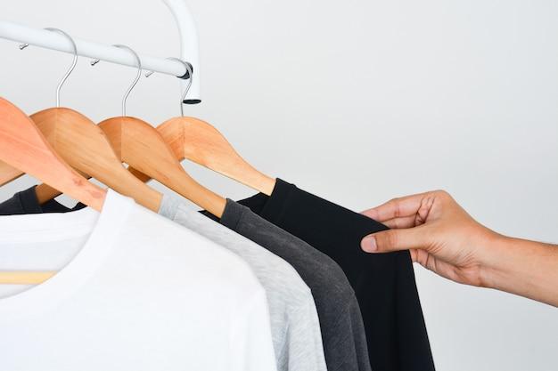 木製ハンガーに黒、グレー、白のtシャツのコレクションから黒い色のtシャツを選択する男の手 Premium写真