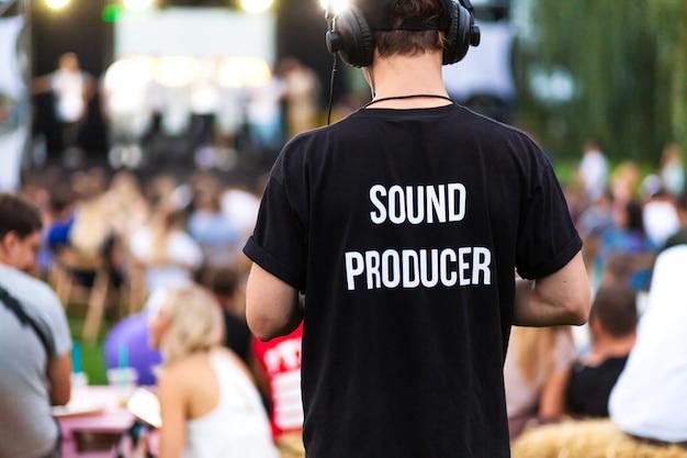 ヘッドフォンと碑文とtシャツの技術者男 Premium写真