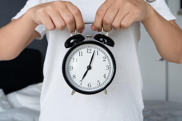 白いtシャツを着た男が、ベルの付いたスタイリッシュな黒の目覚まし時計を持っています。目覚まし時計で、八の始まり。起きる時間です。 Premium写真
