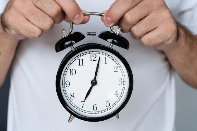 白いtシャツを着た男が、ベル付きのスタイリッシュな黒い目覚まし時計を持っています。目覚まし時計で、八の始まり。起きる時間です。 Premium写真
