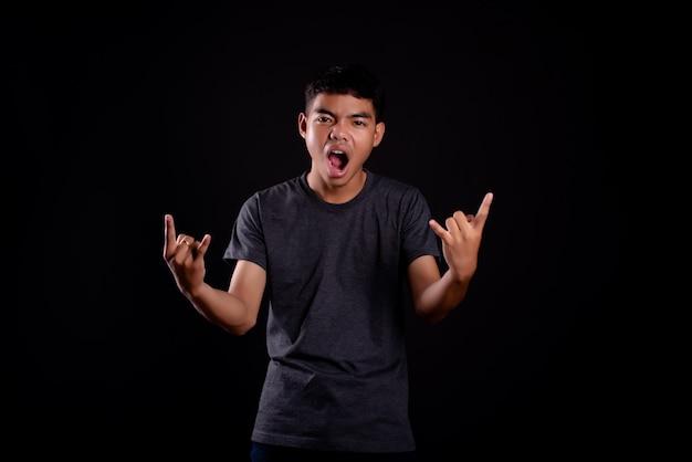 ロッカージェスチャーを作る暗いtシャツの若い男 無料写真