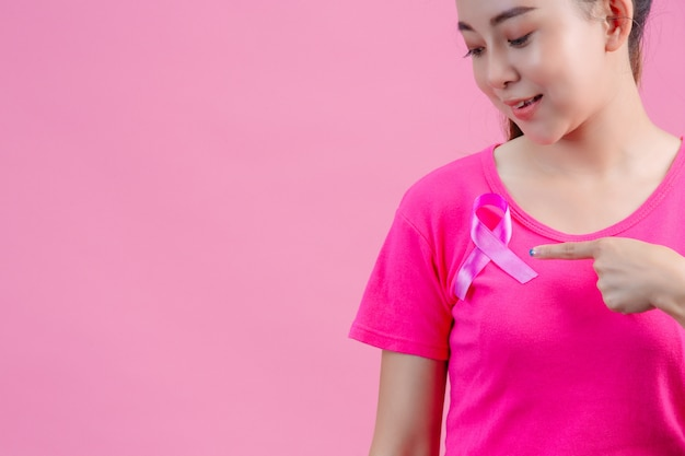 乳がんの意識、胸にサテンのピンクのリボンとピンクのtシャツの女性、シンボル乳がんの意識をサポート 無料写真