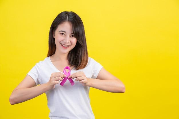 乳がん、胸にサテンのピンクのリボンが付いた白いtシャツの女性、乳がんの意識のシンボル 無料写真