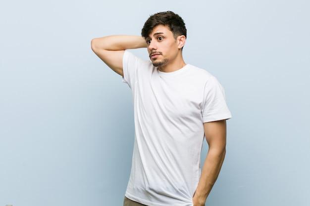 頭の後ろに触れる、考えて、選択をする白いtシャツを着ている若い男 Premium写真