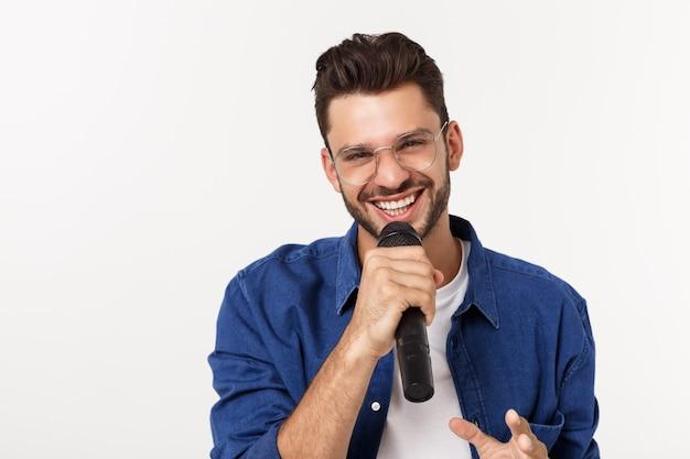 歌う灰色の背景に分離されたtシャツで興奮して若い男の肖像画。 Premium写真