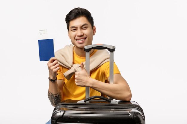 トロリーバッグとパスポートで旅行する準備ができている黄色のtシャツでハンサムな若いアジア人 Premium写真