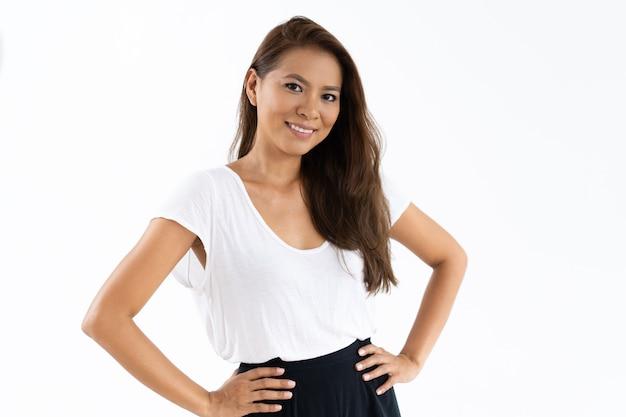 カメラにポーズをとって白いtシャツを着て肯定的な女子学生 無料写真