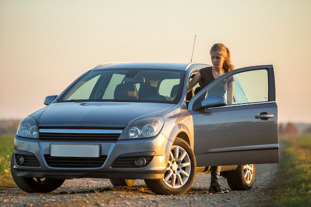 ジーンズと澄んだ明るい空のコピースペースに空の砂利フィールド道路に開いたドアと銀の車でtシャツの若いスリムな魅力的な長髪の女性 Premium写真