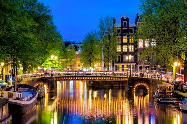 オランダ、オランダの黄t時の典型的なオランダの家と橋のあるアムステルダムの運河。 Premium写真