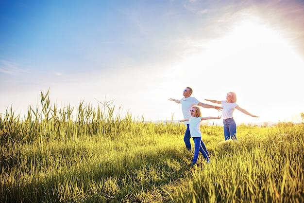 公園で白いtシャツ、サングラス、ジーンズの幸せな家族 Premium写真