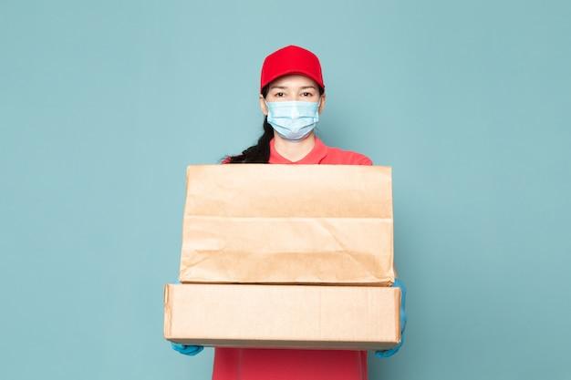 青い壁にボックスを保持しているピンクのtシャツの赤い帽子青い滅菌マスク青い手袋の若い女性の宅配便 無料写真