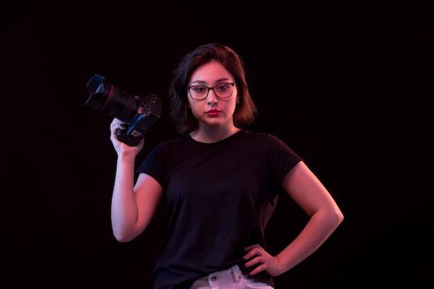 カメラと黒のtシャツの若い女性 無料写真