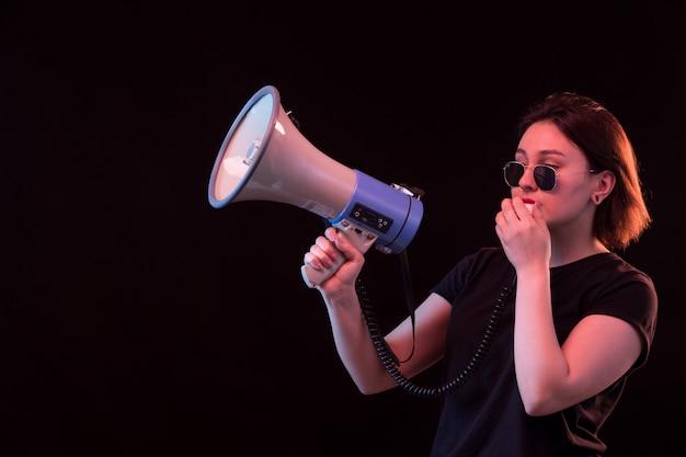 メガホンを保持している黒のtシャツの若い女性 無料写真