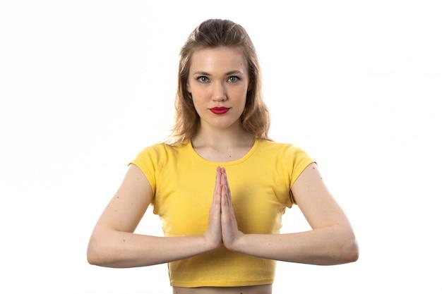 祈っている黄色のtシャツを持つ若いブロンドの女性 無料写真