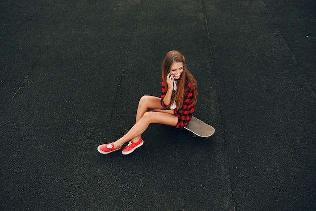 スケートボードの上に座って、白いtシャツ、赤いシャツ、ショートパンツ、スニーカーで完璧な笑顔でかわいい美しい若い女性 Premium写真