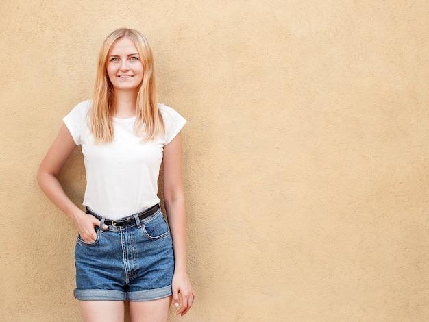 空白の白いtシャツと粗い通りの壁、ミニマルな都市服スタイルに対してポーズジーンズを着て内気な少女 Premium写真