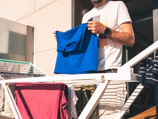 若いひげを生やした男が彼のロフトのテラスで青いtシャツを干す Premium写真