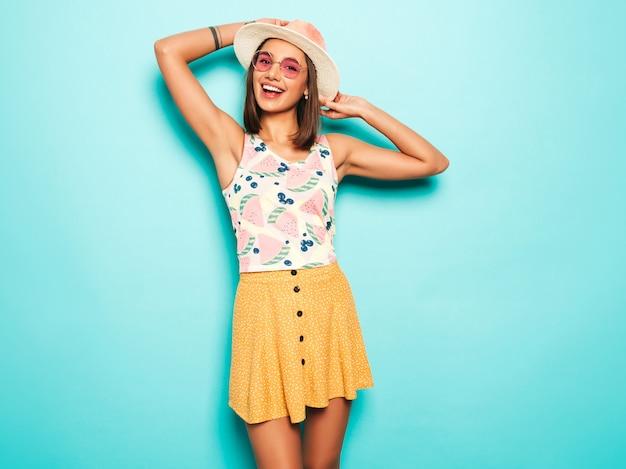 帽子でカメラを見て若い美しい女性。カジュアルな夏の白いtシャツと丸いサングラスの黄色いスカートのトレンディな女の子。肯定的な女性は顔の感情を示しています。青に分離された面白いモデル 無料写真