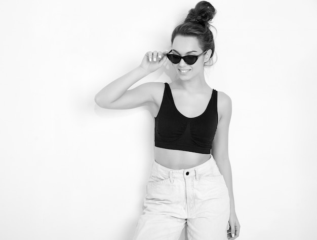 壁に近いポーズ夏tシャツトップとジーンズ服で裸化粧と若いブルネット美人少女モデルの肖像画。 無料写真