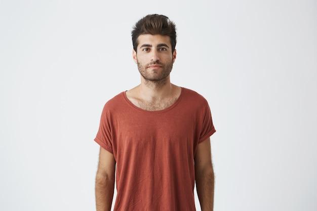茶色の目で見ているカジュアルな赤いtシャツを着ているトレンディなヘアカットのスタイリッシュなひげを生やした男の肖像。見て満足している若いハンサムな男。人と感情の概念 無料写真