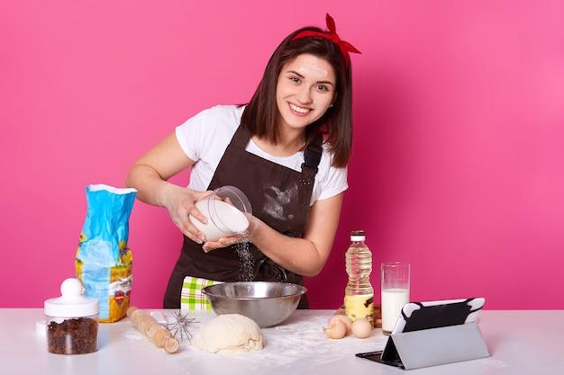 パン屋さんのキッチンでペストリーを作って準備する女性のイメージ。小麦粉ビットを追加します。女性は心地よい顔の表現があり、カメラを直接楽しく見て、パンを焼き、茶色のエプロンとtシャツを着ています。 Premium写真