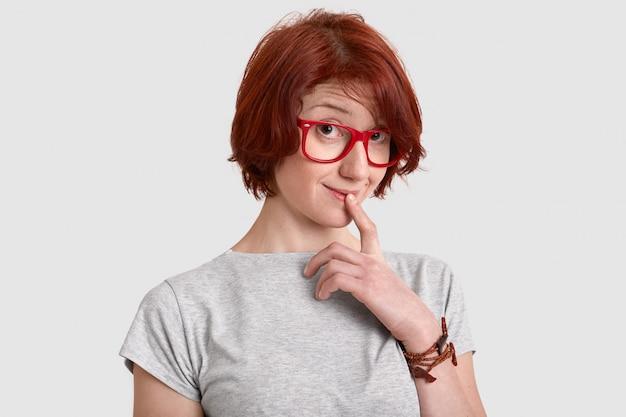 好奇心が強い赤い髪の若い女性は唇に人差し指を保ち、興味を持って見える、赤い縁の眼鏡のカジュアルなtシャツを着て、何かについて夢を見て、白い壁に分離された短い髪型をしています。 無料写真