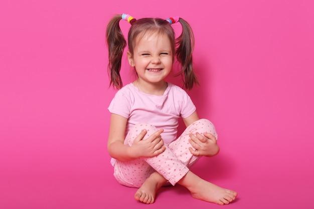床に座って、ピンクに分離されたポーズをとって、バラのtシャツとズボンを着て、ポニーテールを持っている、元気のある室内笑いの肯定的な子供。子供の頃のコンセプトです。 無料写真