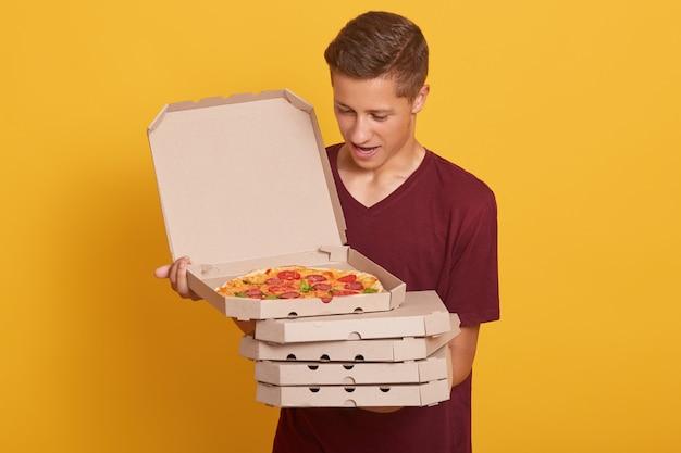 手でピザの箱のスタックを保持しているバーガンディのカジュアルなtシャツを着ているハンサムな男 無料写真