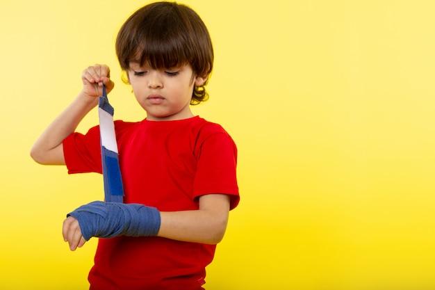黄色の壁に赤いtシャツの青いティッシュで彼の手を結ぶかわいい男の子 無料写真