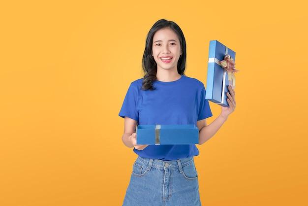 青いtシャツを保持していると、青いギフトを開くで若い笑顔のアジア女性 Premium写真