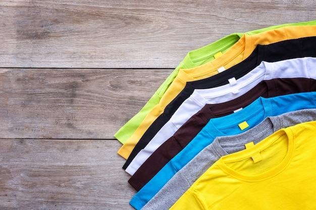 灰色の木の板の背景に色のtシャツのトップビュー Premium写真