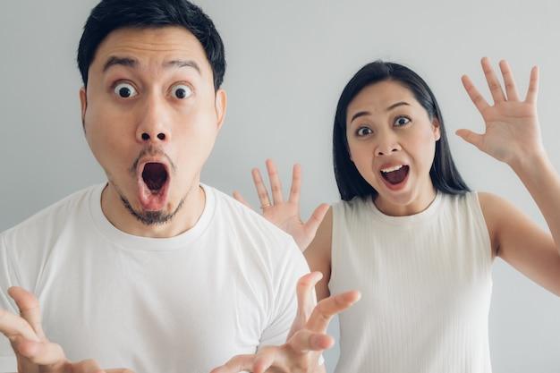 白いtシャツと灰色の背景で驚きとショックを受けたカップルの恋人。 Premium写真