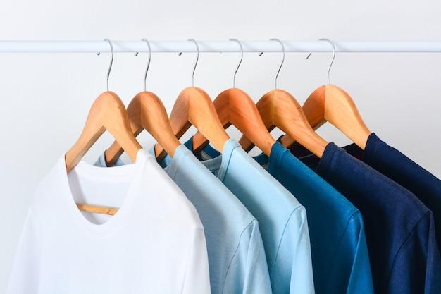 クローゼットや衣服ラックに木製の洋服ハンガーに掛かっている青いトーンカラーtシャツのコレクションシェードを閉じる Premium写真